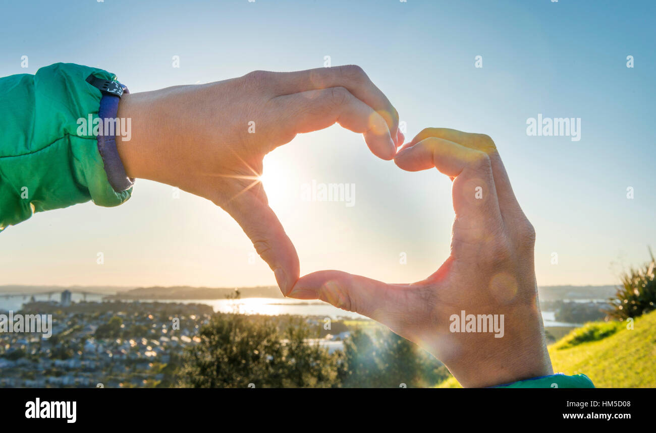 Hands in a heart shape, backlit, Auckland Region, North Island, New Zealand - Stock Image