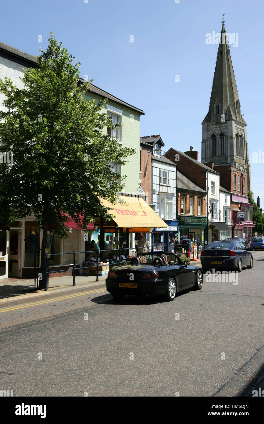 View of the High Street, Market Harborough, Leicestershire with the tower of St Dionysius church - Stock Image