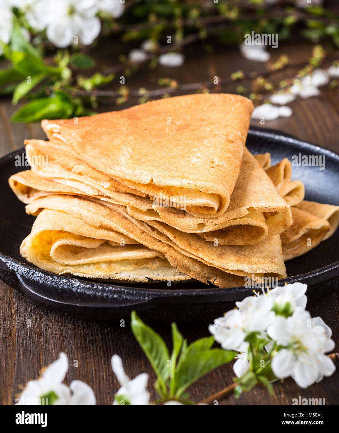 Homemade crepes  folded in triangles on frying pan on spring blossom background - Stock Image
