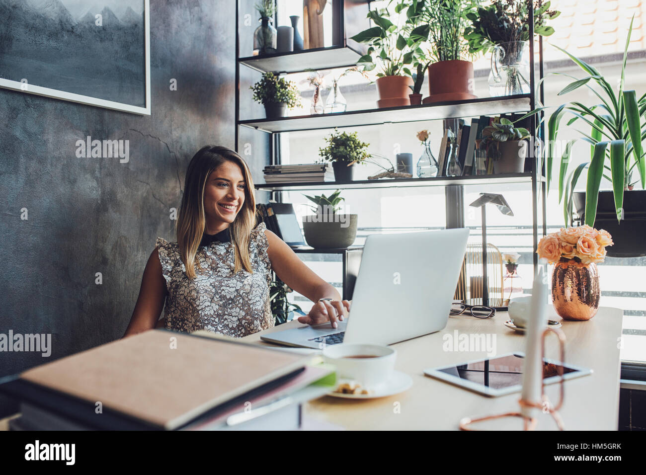 Smiling businesswoman working on laptop at home office - Stock Image