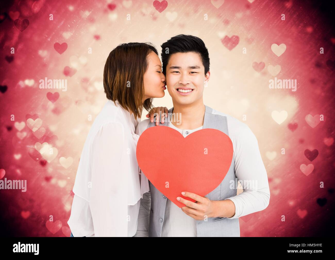 Woman kissing on man cheeks while holding red heart - Stock Image