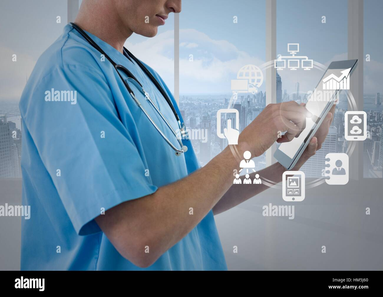 Male nurse using digital tablet with app icon interface screen - Stock Image