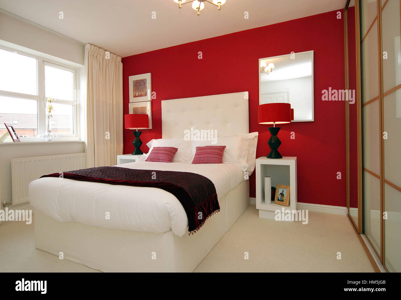 Modern Bedroom With Sliding Wardrobe Doors, Red Feature Wall, Modern Stock Photo: 132890027