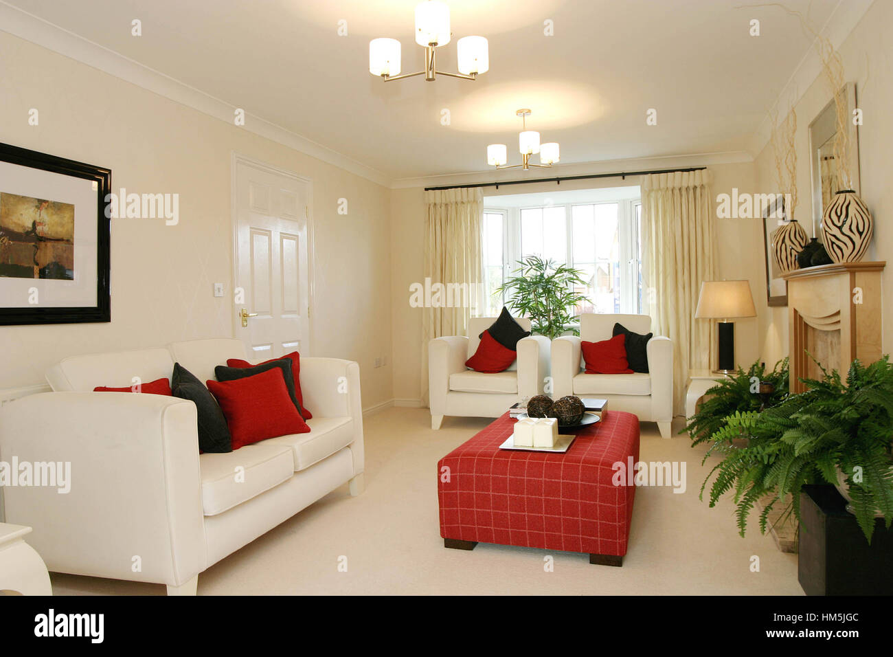 Modern living room interior, cream sofas, red soft furnished coffee table, neautral colouring. - Stock Image