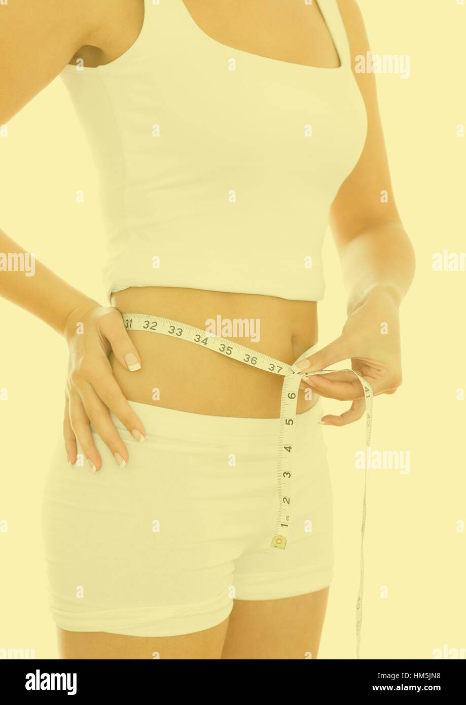 Woman measuring waste with measuring tape - Stock Image