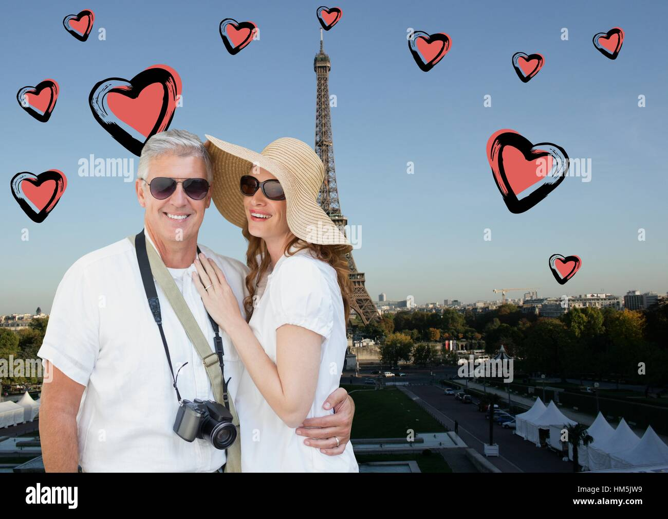 Composite image of couple standing against digitally generated eiffel tower and hearts - Stock Image