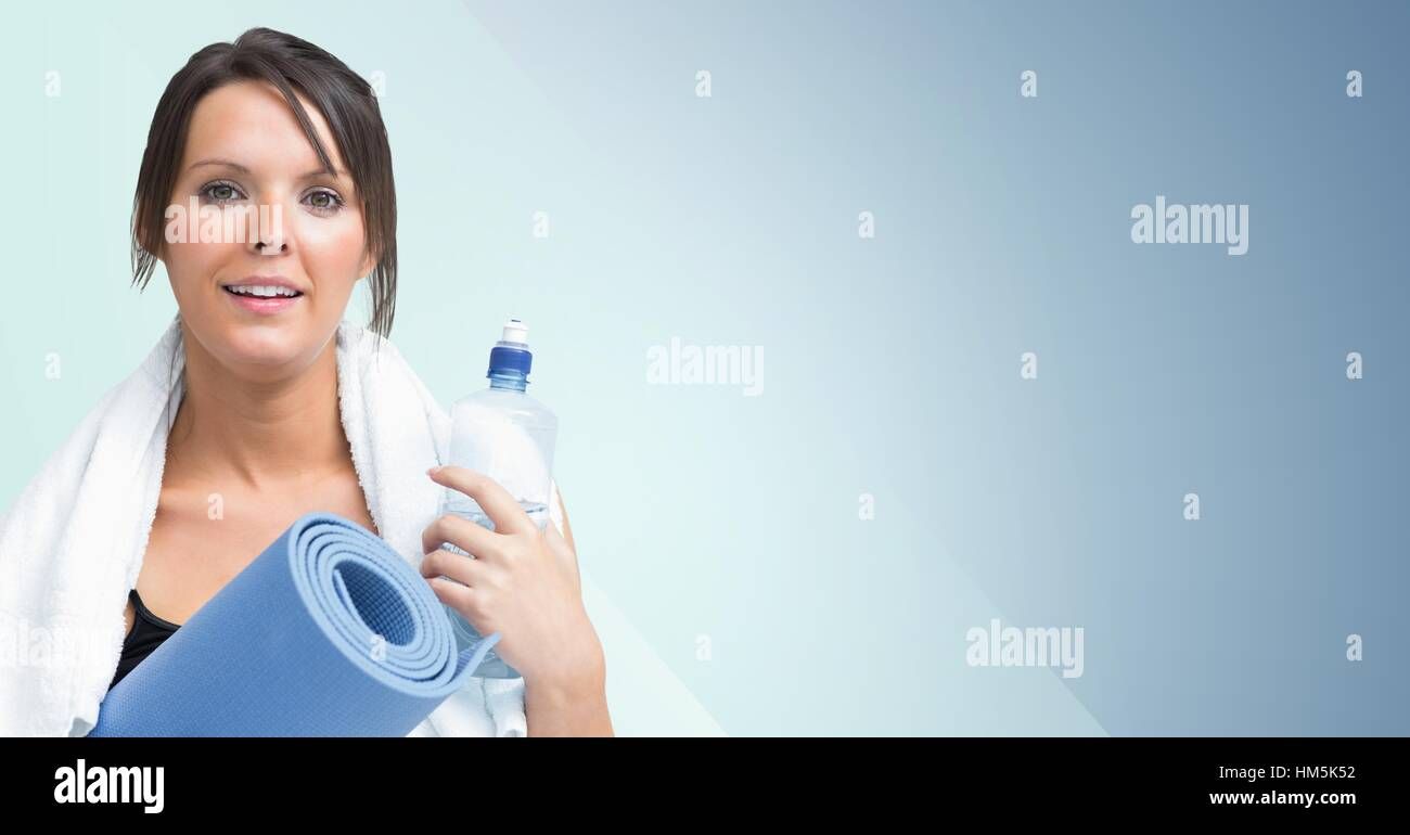 Portrait of fit woman standing with exercise mat and water bottle - Stock Image