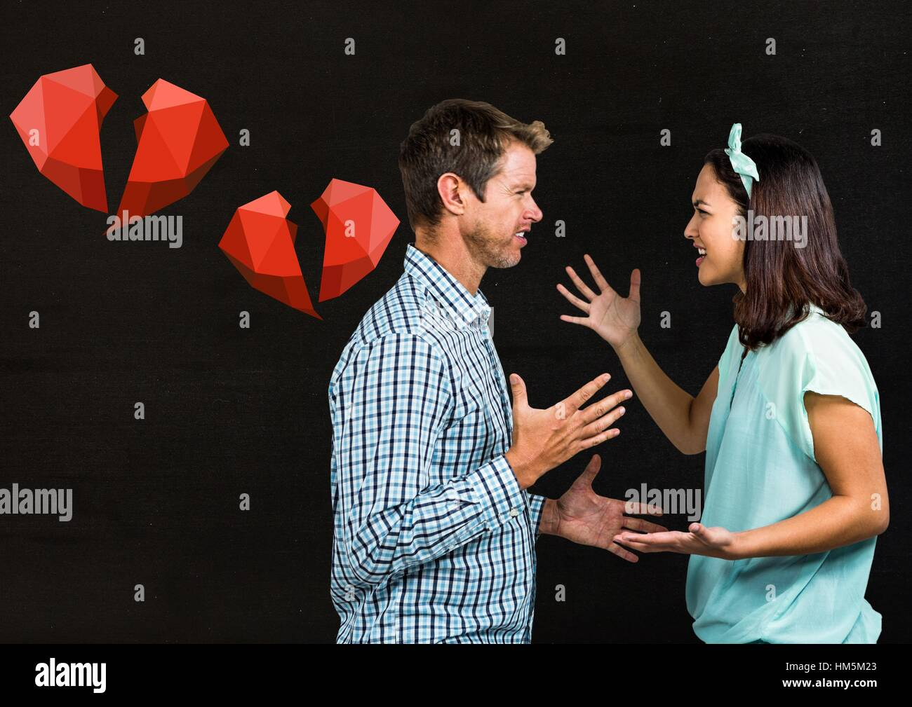 Couple arguing with each other against black background - Stock Image