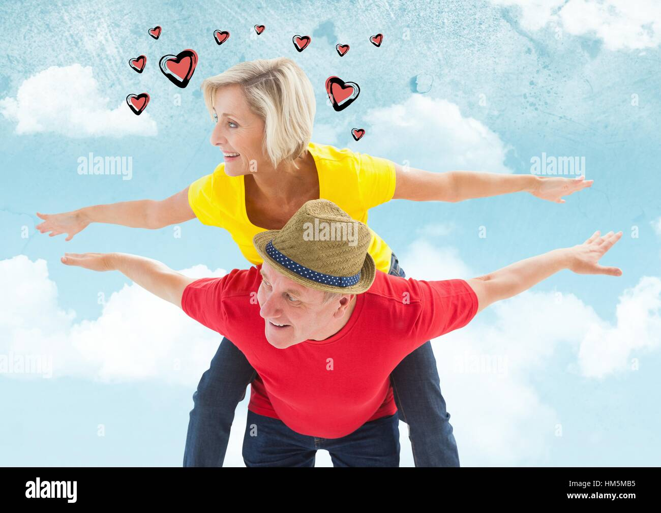 Mature man giving piggy back to woman - Stock Image