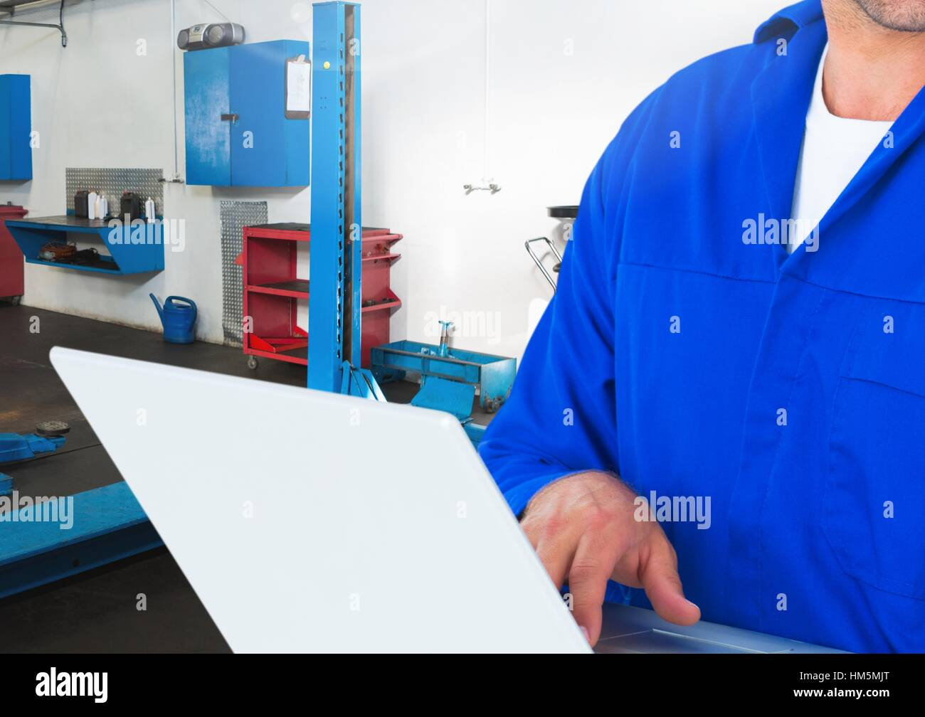 Mid section of mechanic using laptop - Stock Image