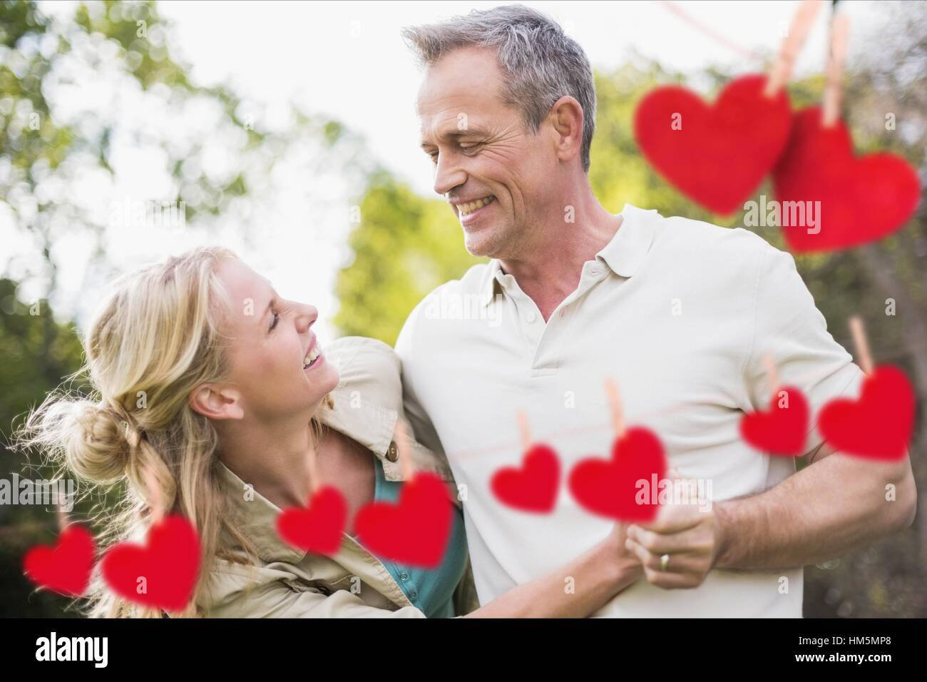 Couple having fun with red hanging hearts - Stock Image