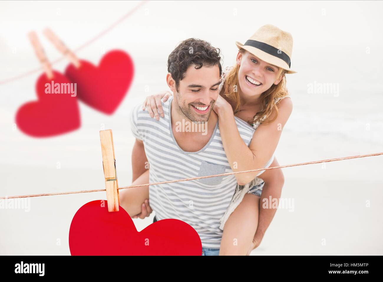 Composite image of red hanging hearts and man giving piggyback to woman - Stock Image