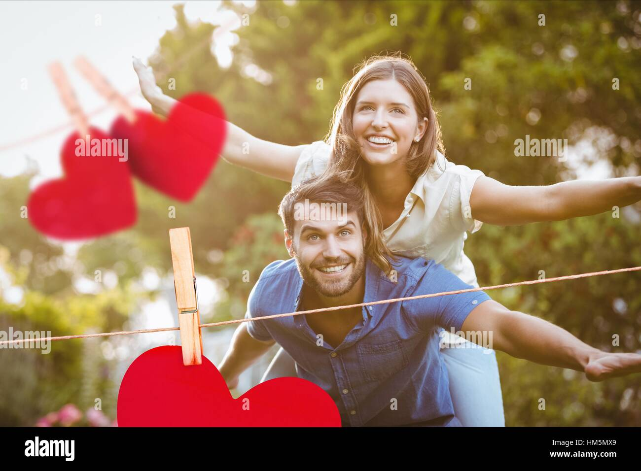 Man giving a piggyback ride to woman - Stock Image