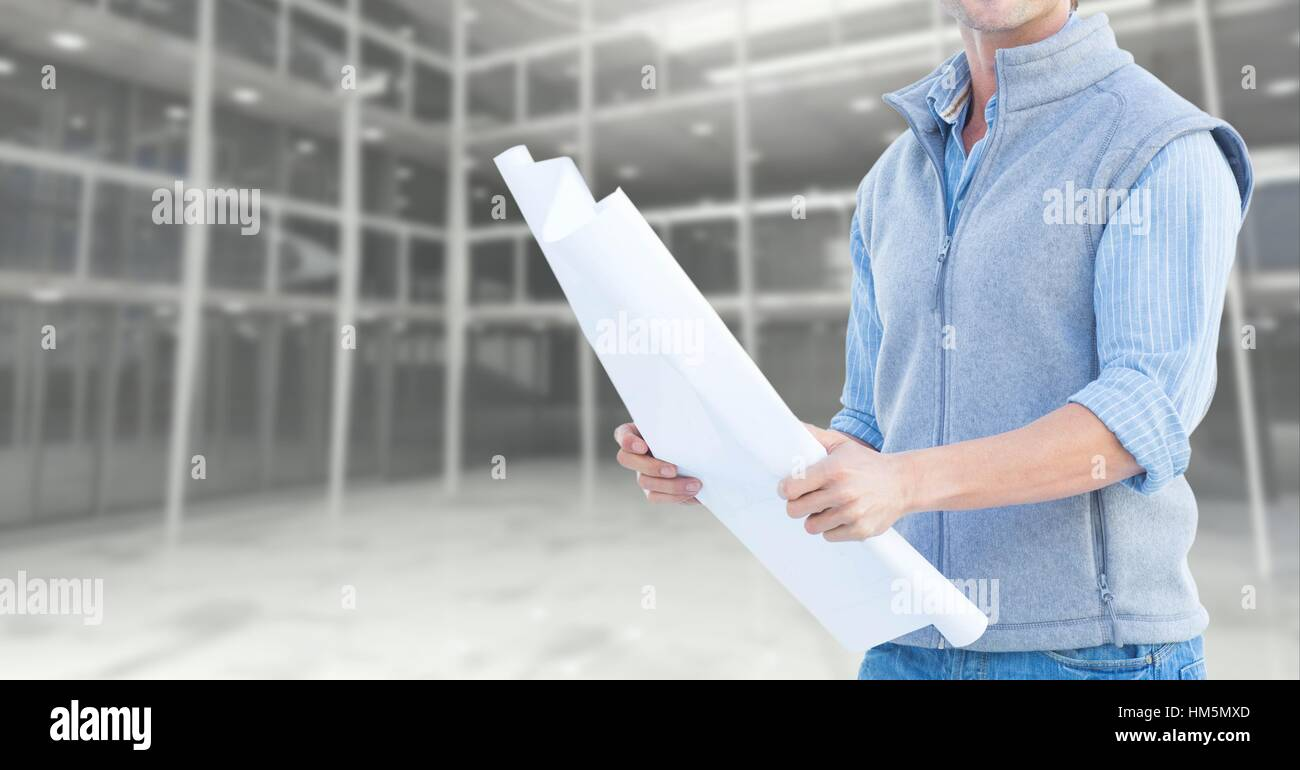 Mid section of construction engineer holding a plan - Stock Image