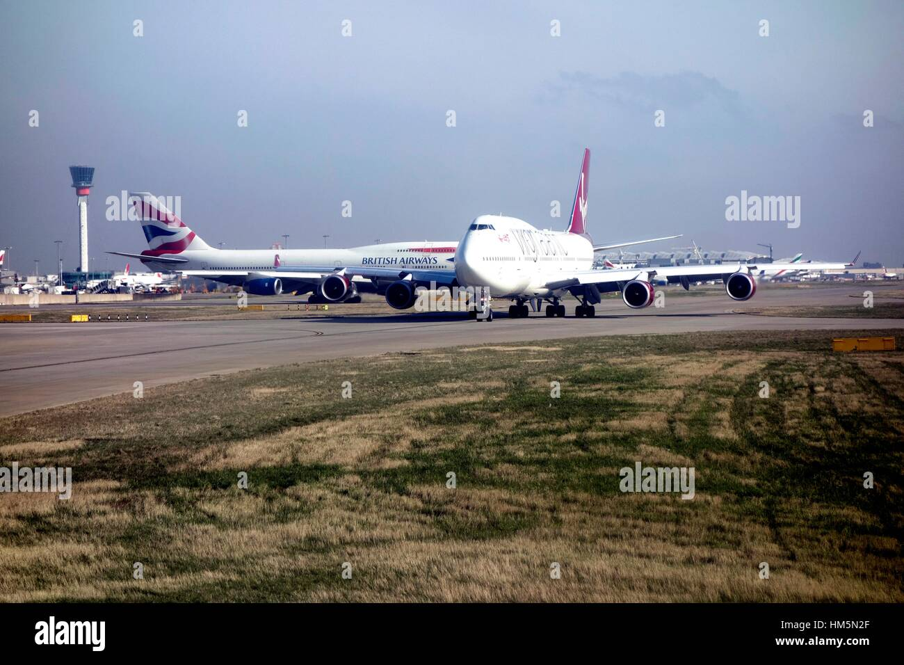 Airplanes queue for a takeoff slot at London Heathrow - Stock Image