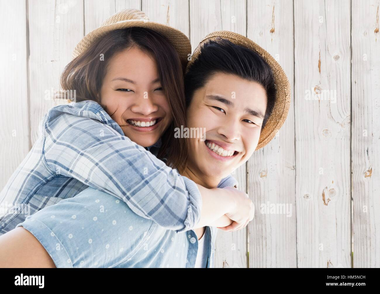 Portrait of man giving piggy back to woman - Stock Image