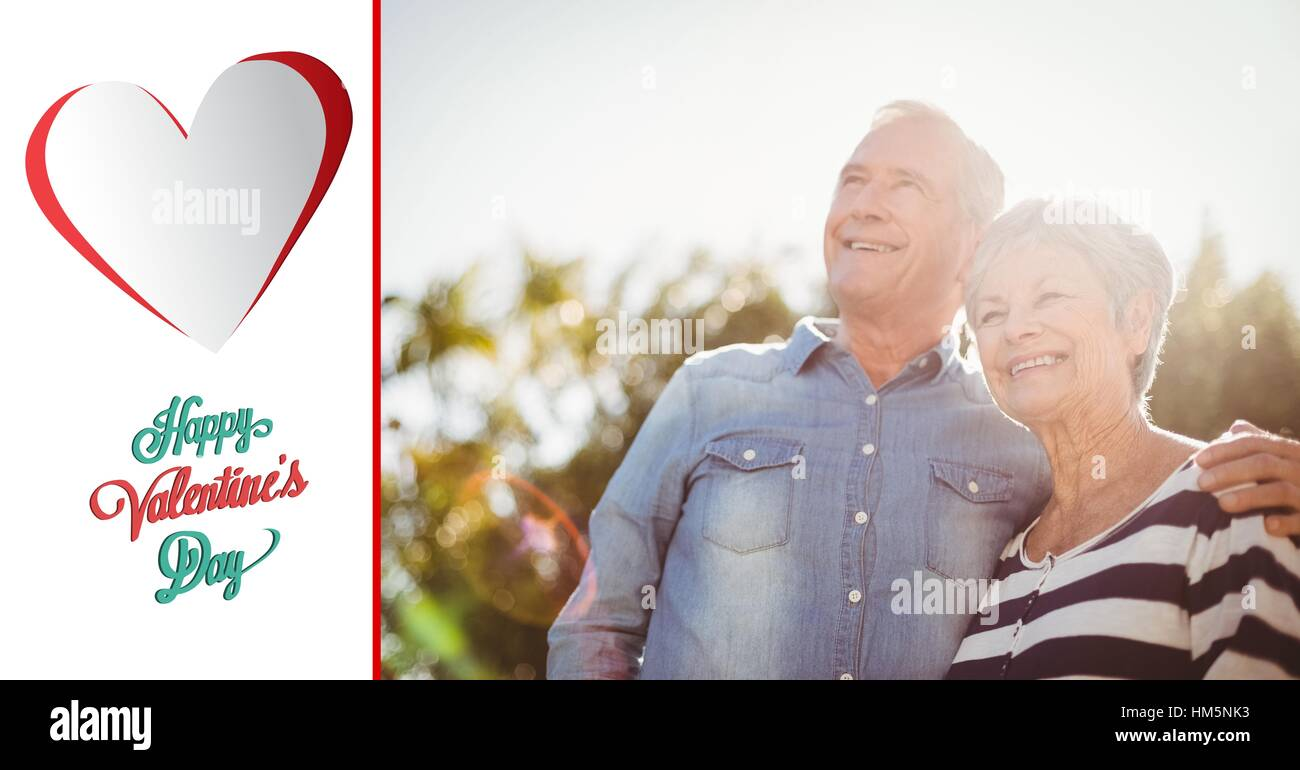 Happy senior couple standing with arm around on a sunny day - Stock Image