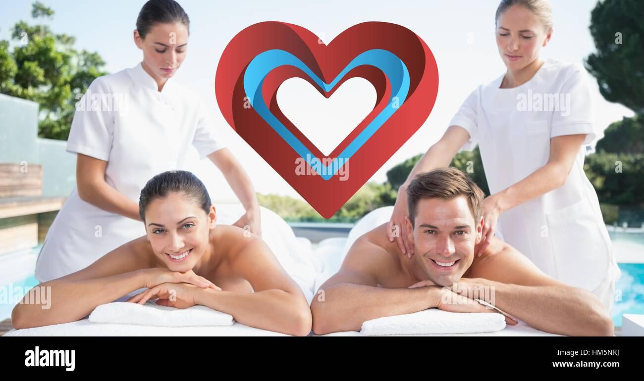 Masseurs giving massage to happy couple Stock Photo