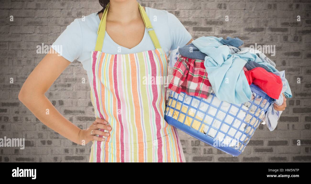 Woman holding a basket full of clothes - Stock Image