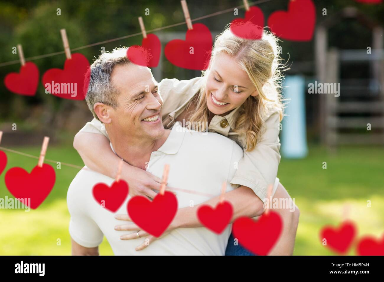 Composite image of red hanging heart and man giving a piggyback to woman - Stock Image
