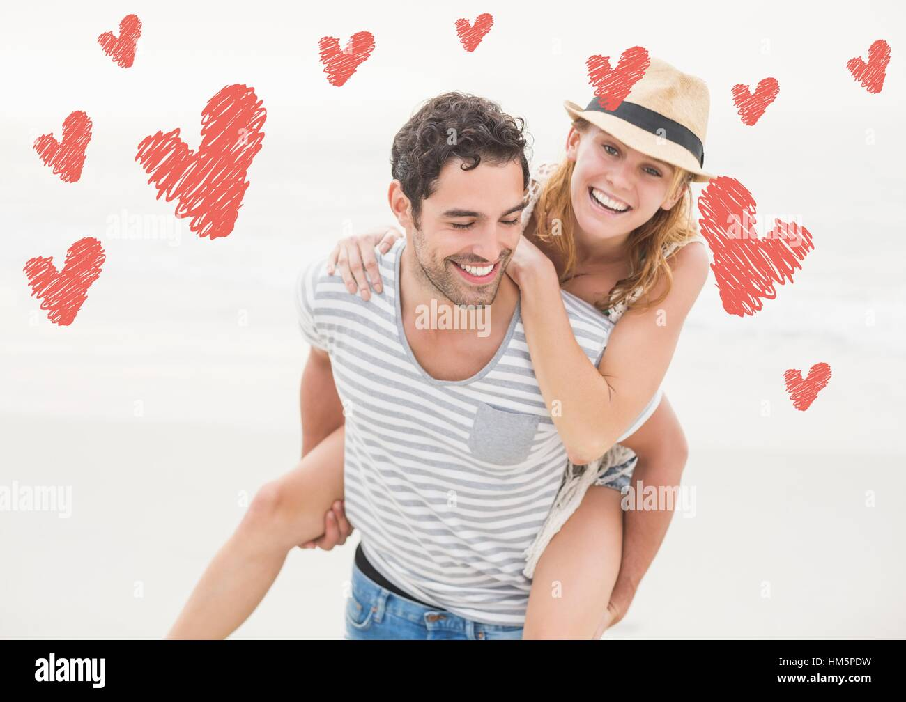 Happy man giving piggy back to woman - Stock Image