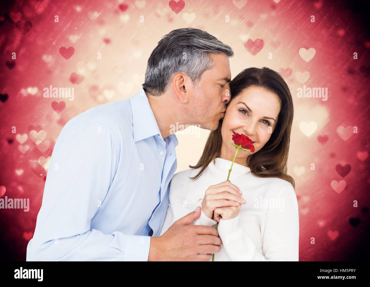 Man kissing on woman cheeks while holding red rose - Stock Image