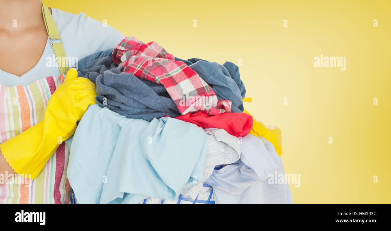 Mid section of woman holding bucket full of clothes - Stock Image