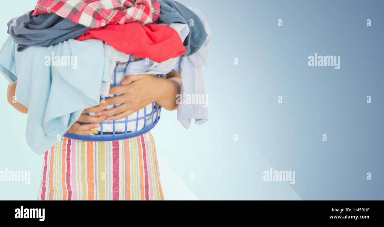 Mid section of woman holding basket full of clothes - Stock Image