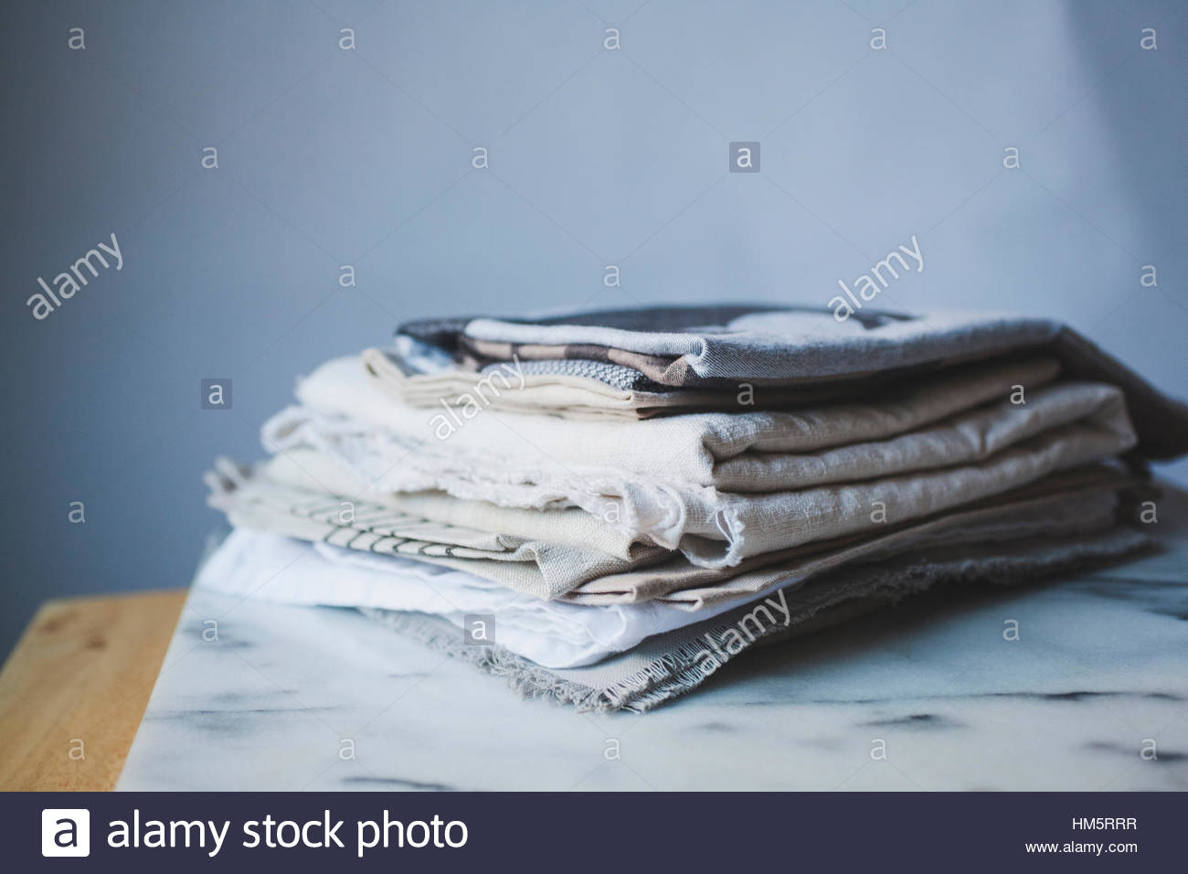 Tablecloths on table by wall - Stock Image