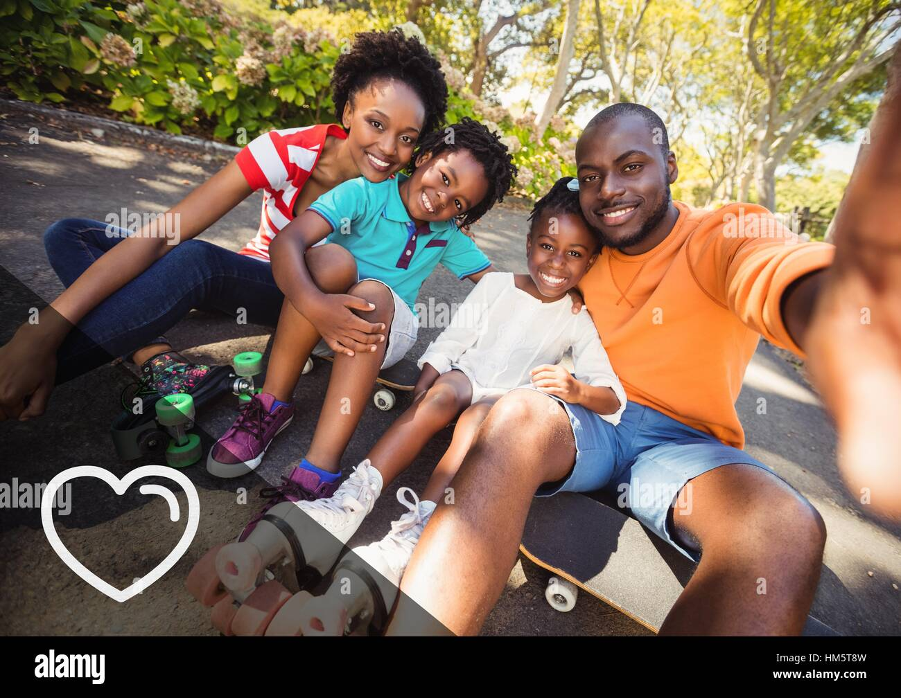 Portrait of happy family sitting on skate board - Stock Image