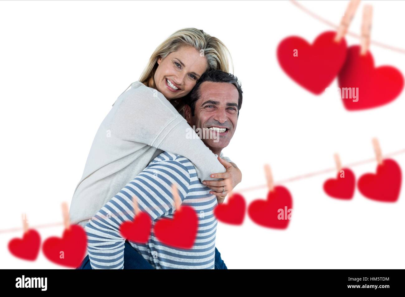 Happy man giving piggyback to woman - Stock Image