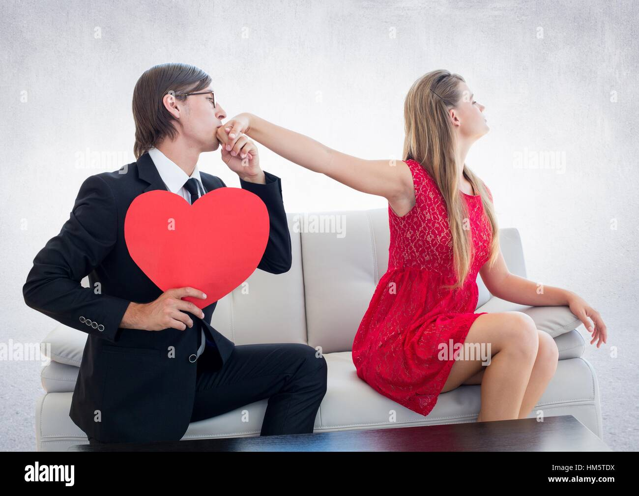 Man with red heart pleasing upset woman - Stock Image