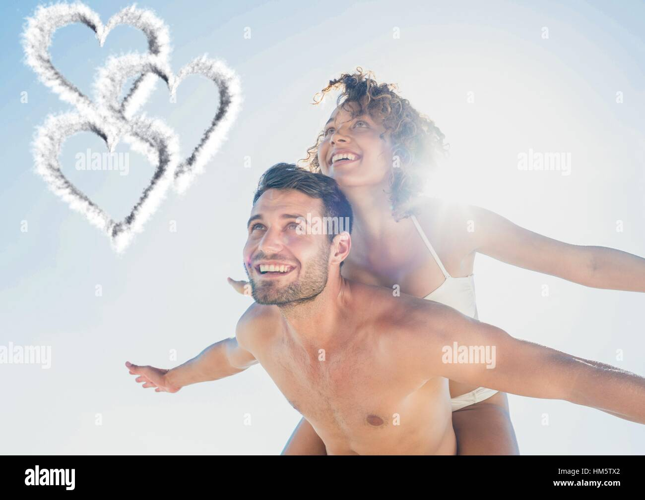 Composite image of man giving piggy back to woman - Stock Image