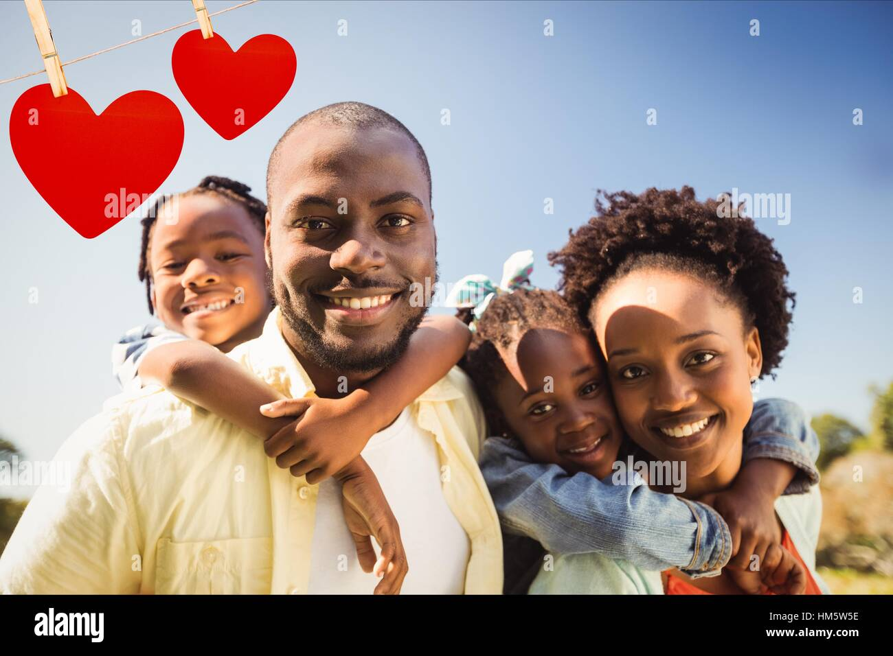 Happy parents giving piggyback to their children - Stock Image