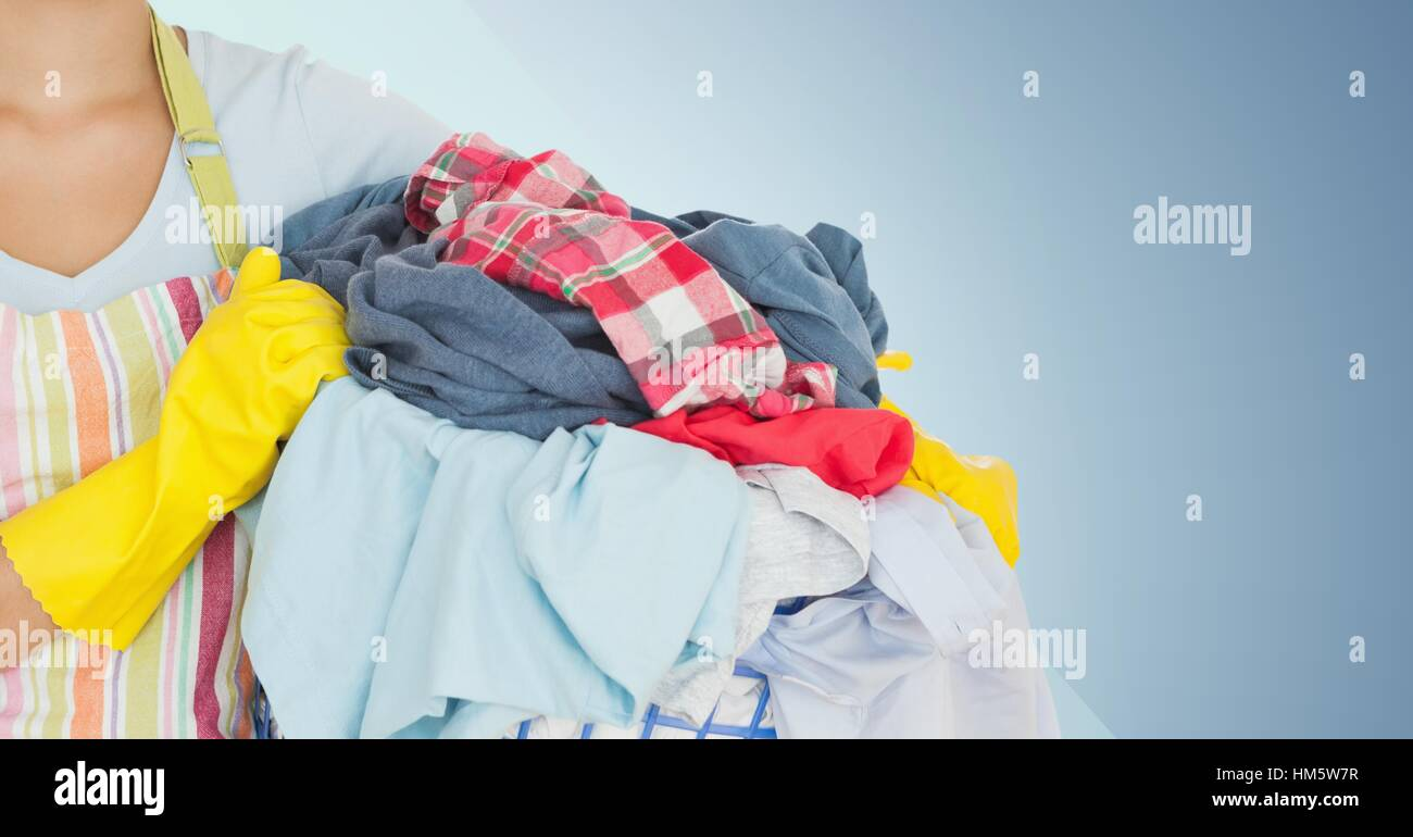 Mid section of female cleaner holding laundry basket filled with clothing - Stock Image
