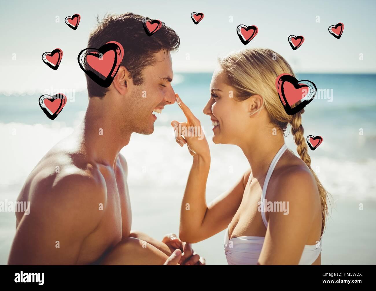 Woman applying moisturizer cream on mans nose at beach - Stock Image