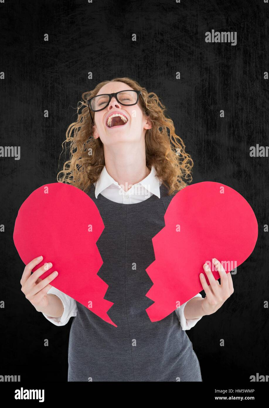 Depressed woman holding broken heart against grey background - Stock Image
