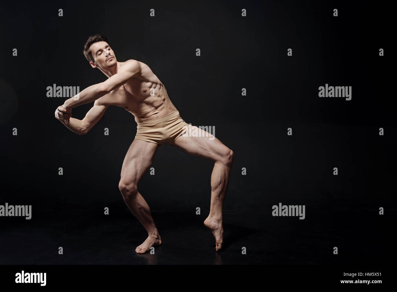 Springy athlete dancing in the black colored studio - Stock Image