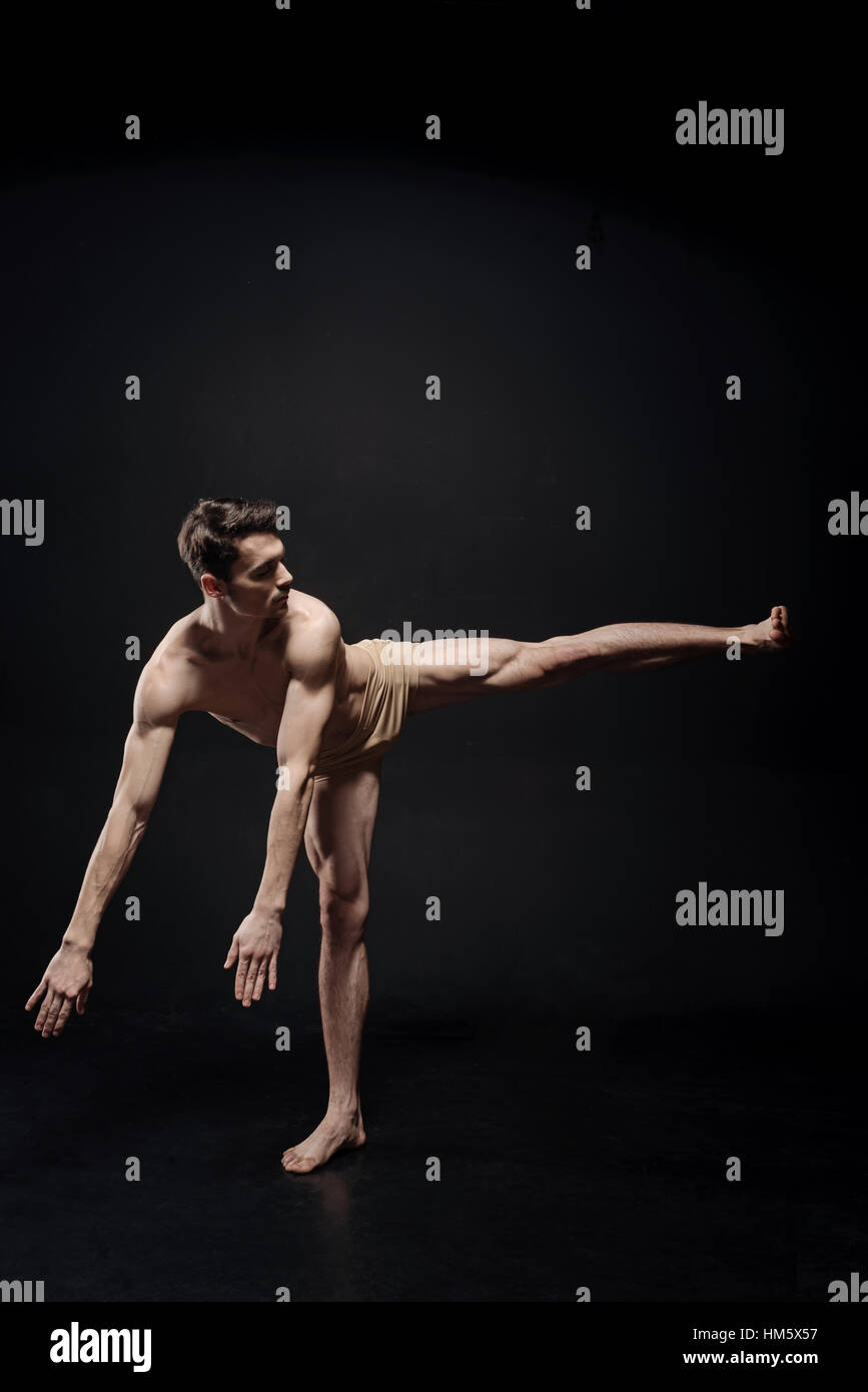 Young athlete dancing in the black colored studio - Stock Image