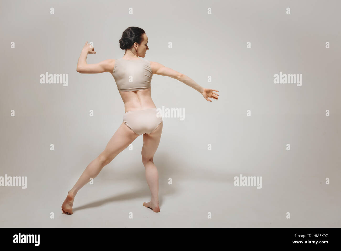 Flexible young ballet dancer performing near the white wall - Stock Image