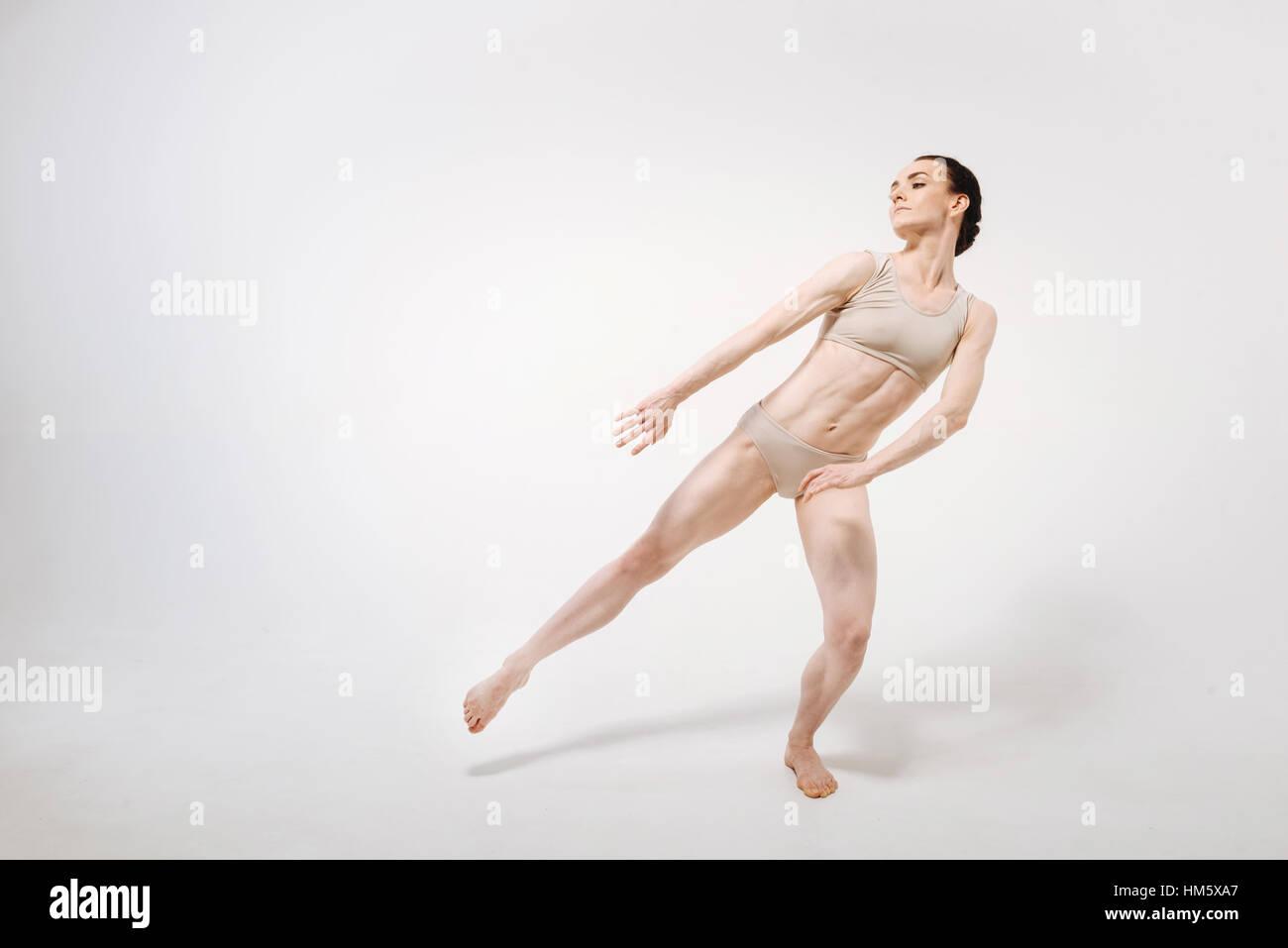 Slim gracious young ballet dancer dancing in the studio - Stock Image