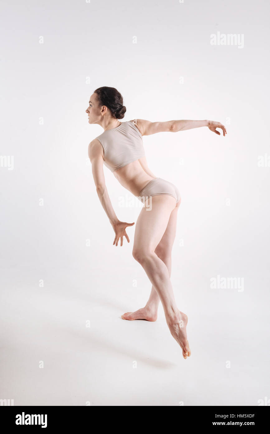 Strong young gymnast dancing against white background Stock Photo