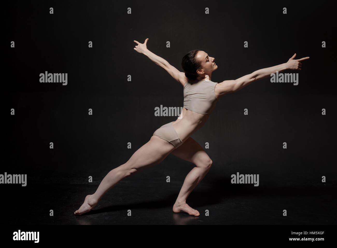 Airy young ballet dancer posing in the studio - Stock Image