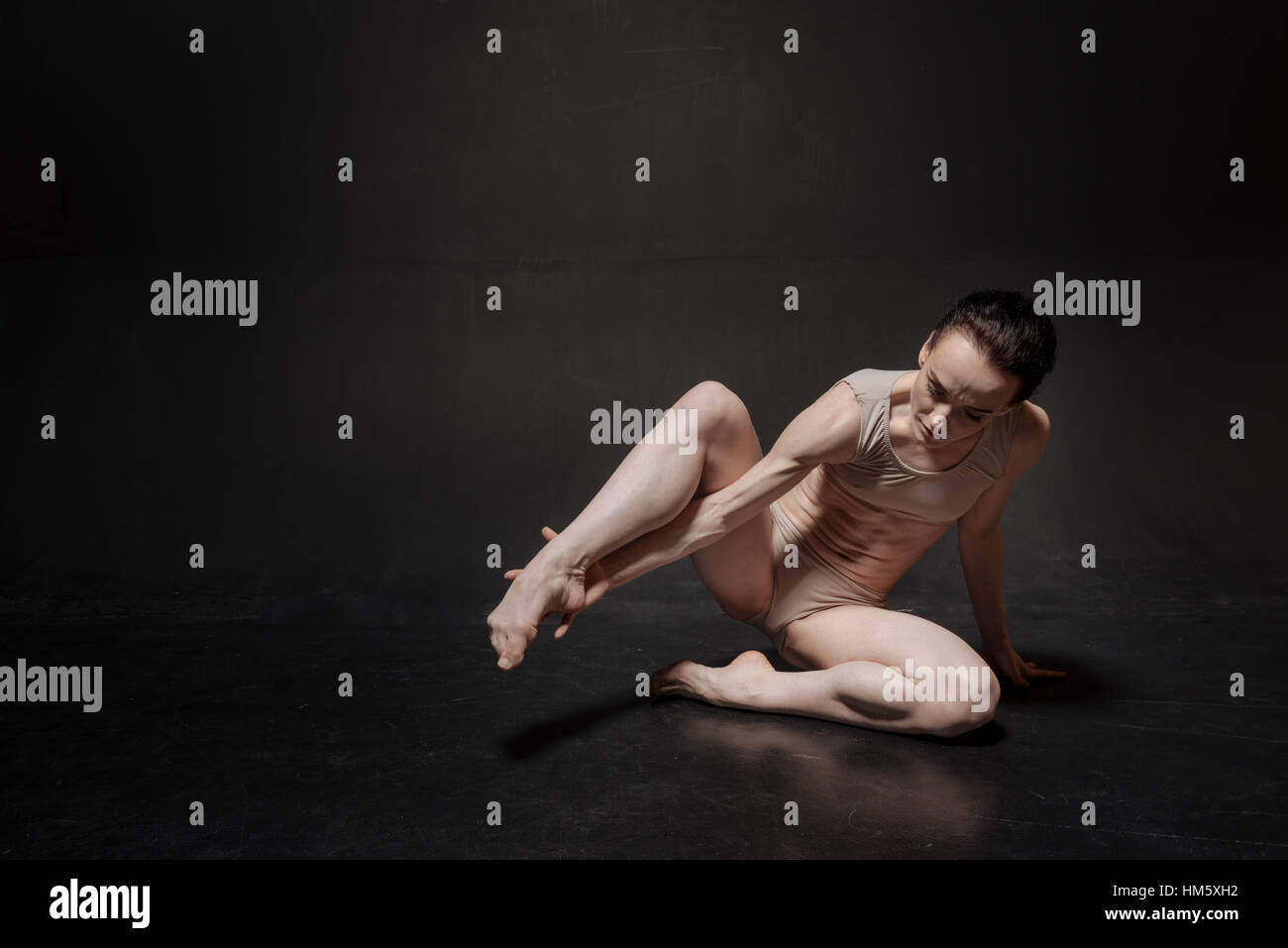 Unemotional young ballet dancer stretching in the studio - Stock Image