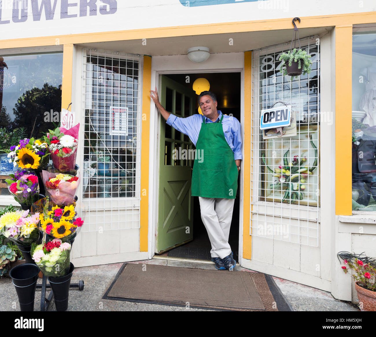 Portrait of male florist standing in doorway of flower shop - Stock Image