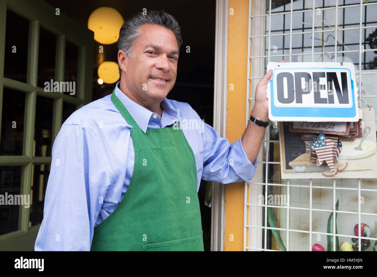 Portrait of male florist holding open sign - Stock Image