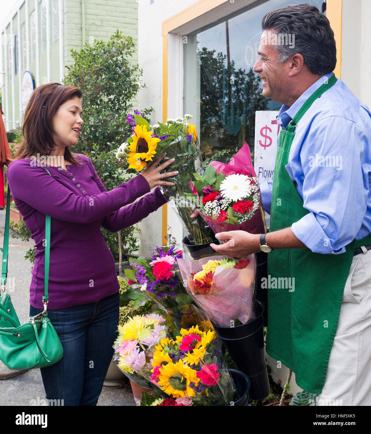 Woman choosing flowers with florist - Stock Image