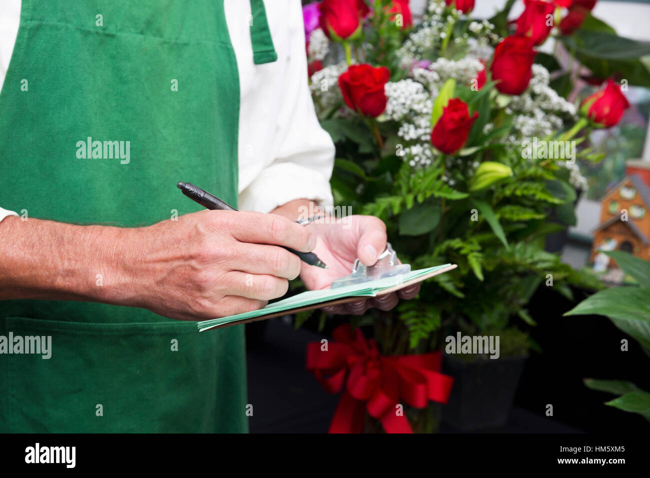 Florist writing down order - Stock Image
