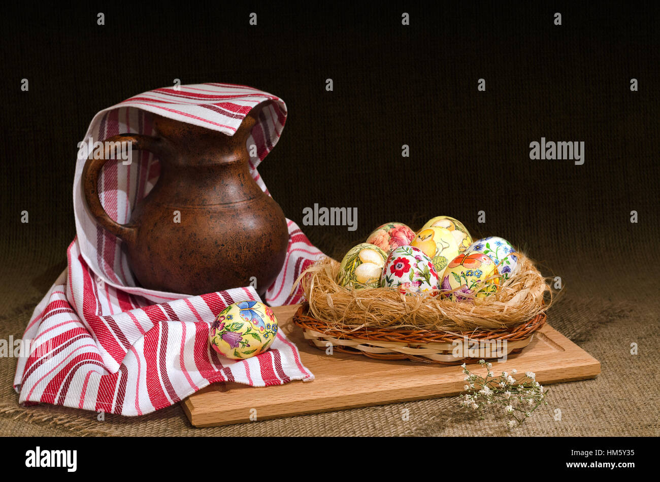 Decoupage Easter eggs in a basket and  jug under the towel. Selective focus. Stock Photo