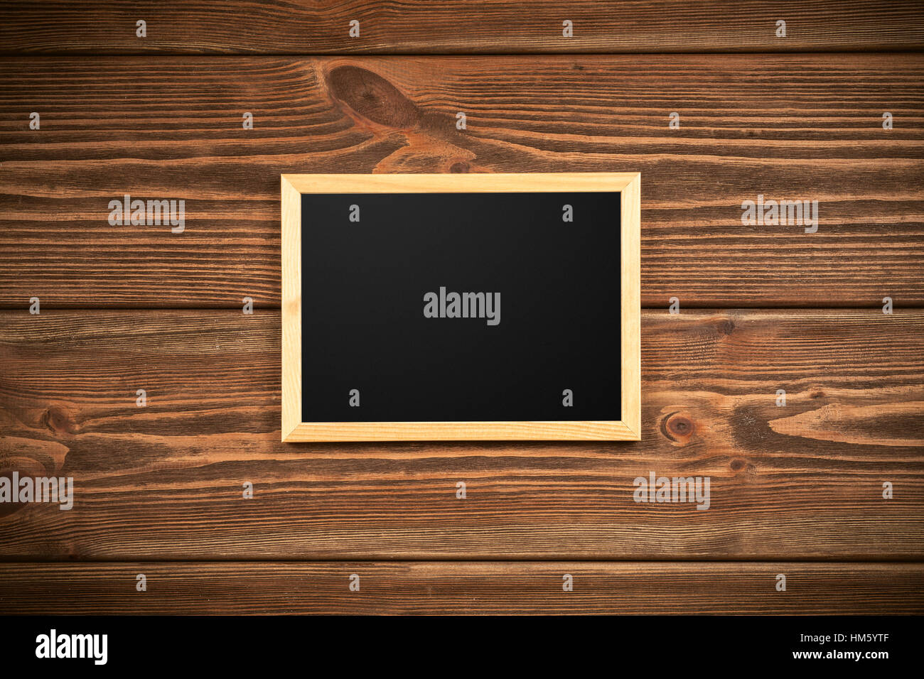 Picture frame on a wooden wall - Stock Image